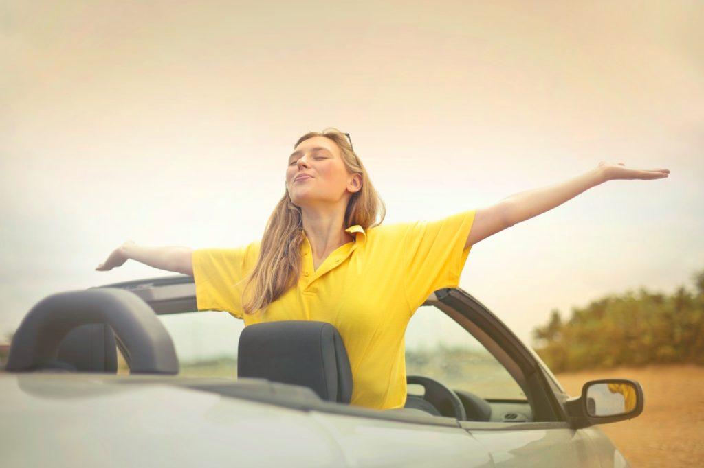 Eine Frau streckt sich aus einem Cabriolet