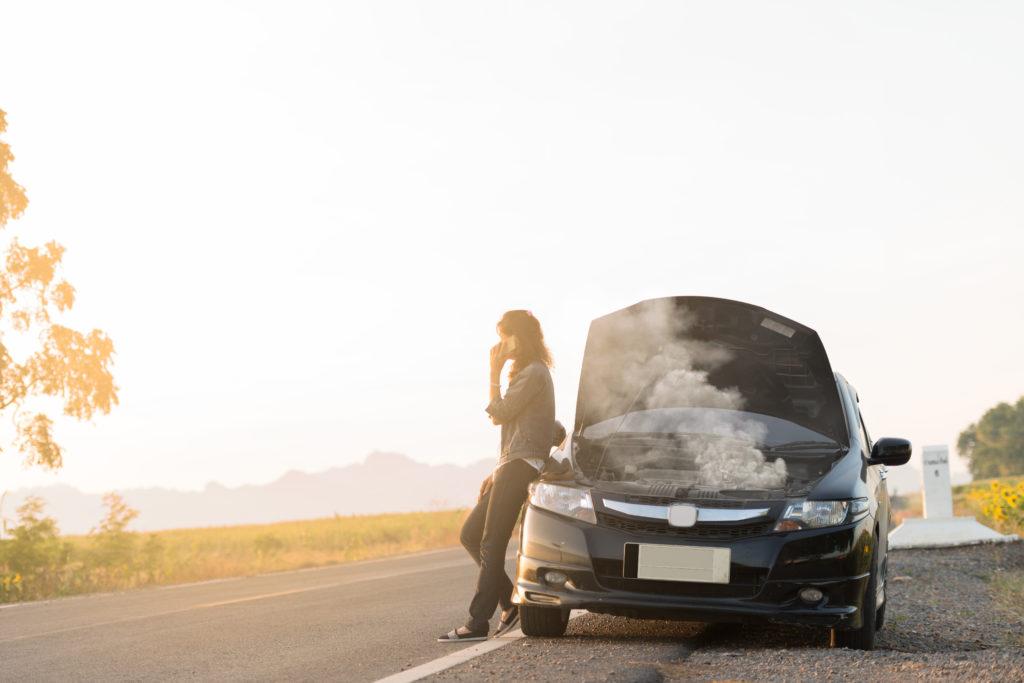 Frau steht mit einer Autopanne am Straßenrand und telefoniert
